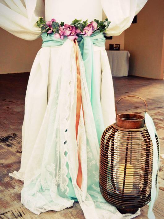 Οι κολώνες στολισμένες με τις κουρτίνες και με λουλούδια, κορδέλες, δαντέλες και υφάσματα