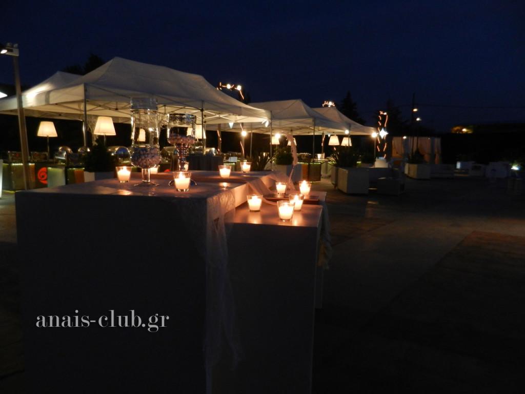 Ο εξωτερικός χώρος, με τους μπουφέδες κάτω από τις τέντες, το γεμάτο κεριά τραπέζι ευχών και στο βάθος το φωτισμένο ιδιαίτερο εκκλησάκι του Anais club