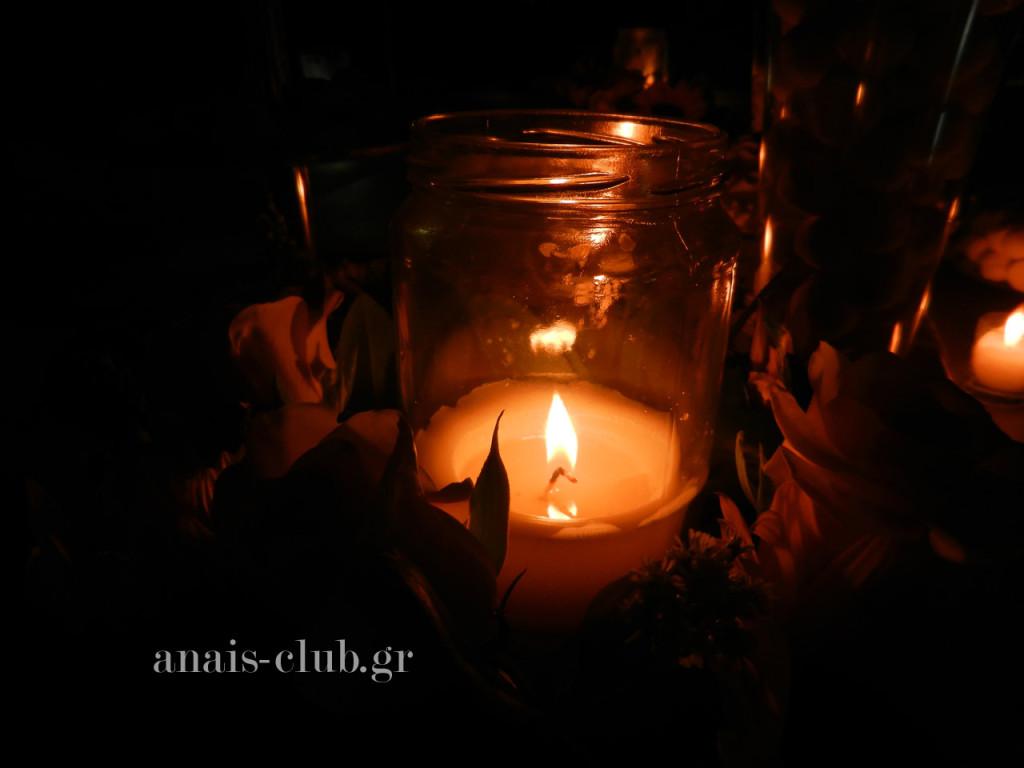 Ρομαντική διακόσμηση στο τραπέζι ευχών με ανθοσυνθέσεις και κεριά σε γυάλινα βάζα