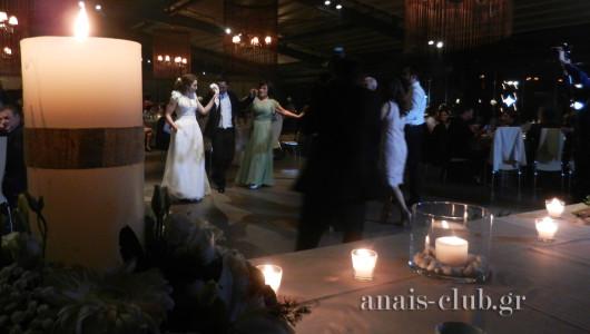 Η νύφη, ο γαμπρός και οι οικογένειες χορεύουν μπροστά από το νυφικό τραπέζι που στολίζεται και με τις λαμπάδες γάμου