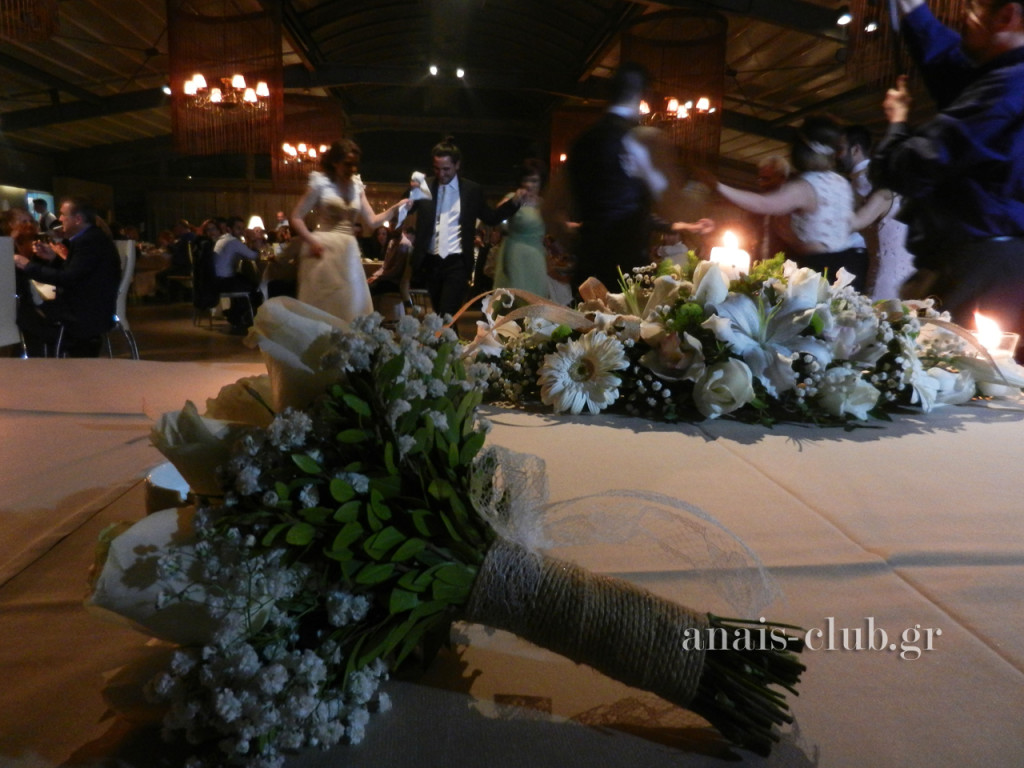 Συνθέσεις λουλουδιών στόλιζαν το νυφικό τραπέζι και η νυφική ανθοδέσμη στέκει στη θέση της νύφης, όσο εκείνη χορεύει με τον γαμπρό και τους καλεσμένους τους
