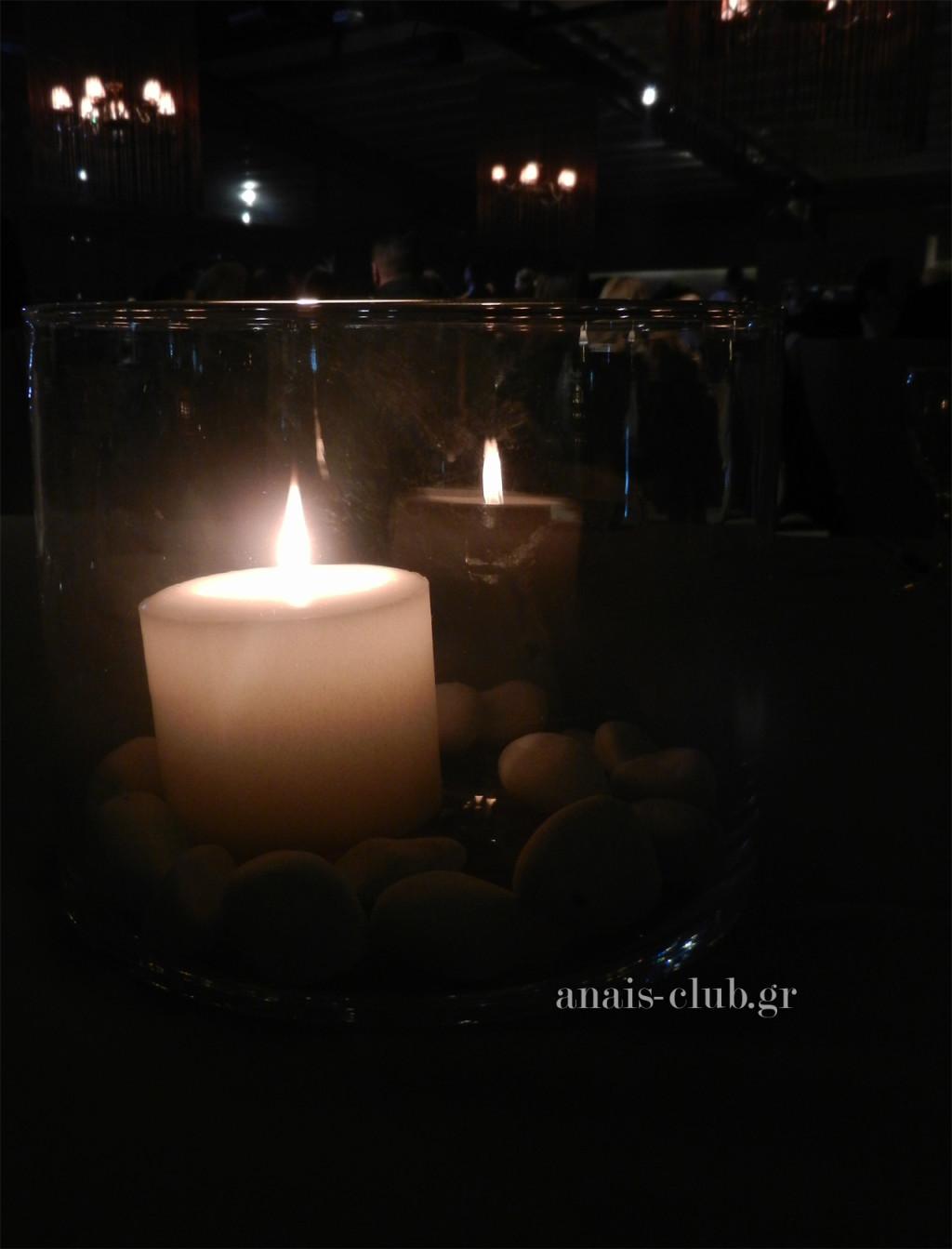 Απλός και ρομαντικός ο στολισμός των τραπεζιών των καλεσμένων, με τις κυλινδρικές γυάλες μας να έχουν στο κέντρο τους λευκά κεριά, που περιβάλλονται από λευκά βότσαλα