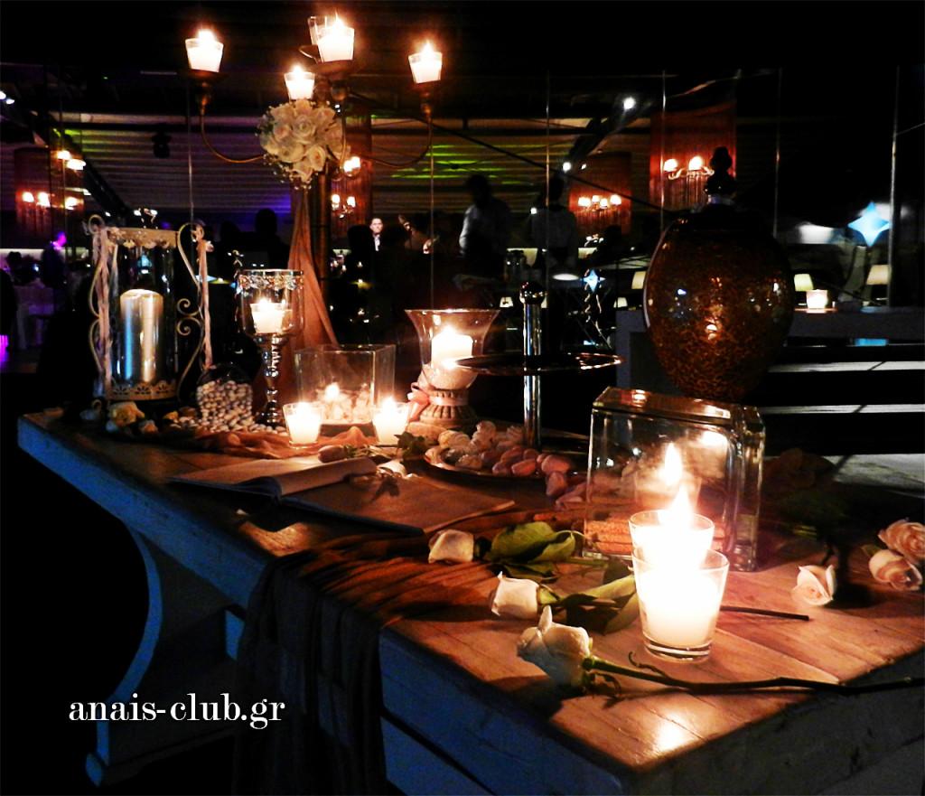Όμορφα αντικείμενα, κεριά σε γυάλες κι ένα ψηλό κηροπήγιο διακοσμούν το τραπέζι ευχών