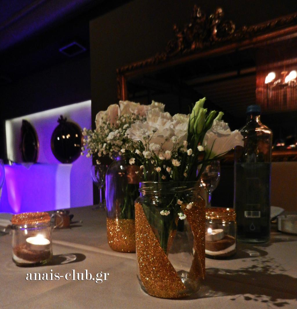 Το centerpiece των τραπεζιών των καλεσμένων ήταν μια σύνθεση από βάζα με φρέσκα λευκά λουλούδια και μικρότερα με λίγη άμμο και κεράκια. Το χρυσό χρώμα ήταν το χαρακτηριστικό τους