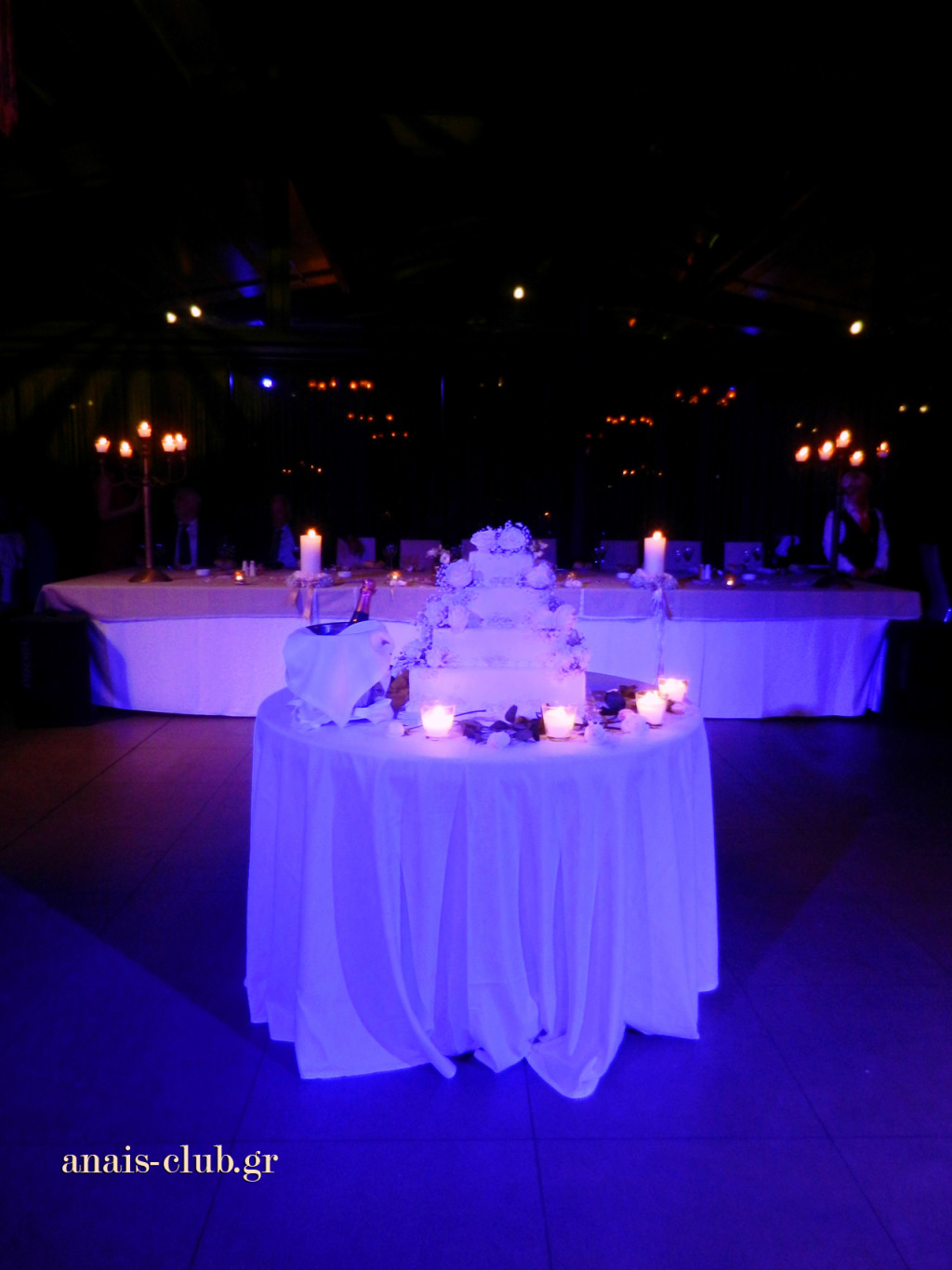 Το τραπέζι με την γαμήλια τούρτα μπροστά από το νυφικό τραπέζι, αλλάζει χρώματα ανάλογα με τον φωτισμό