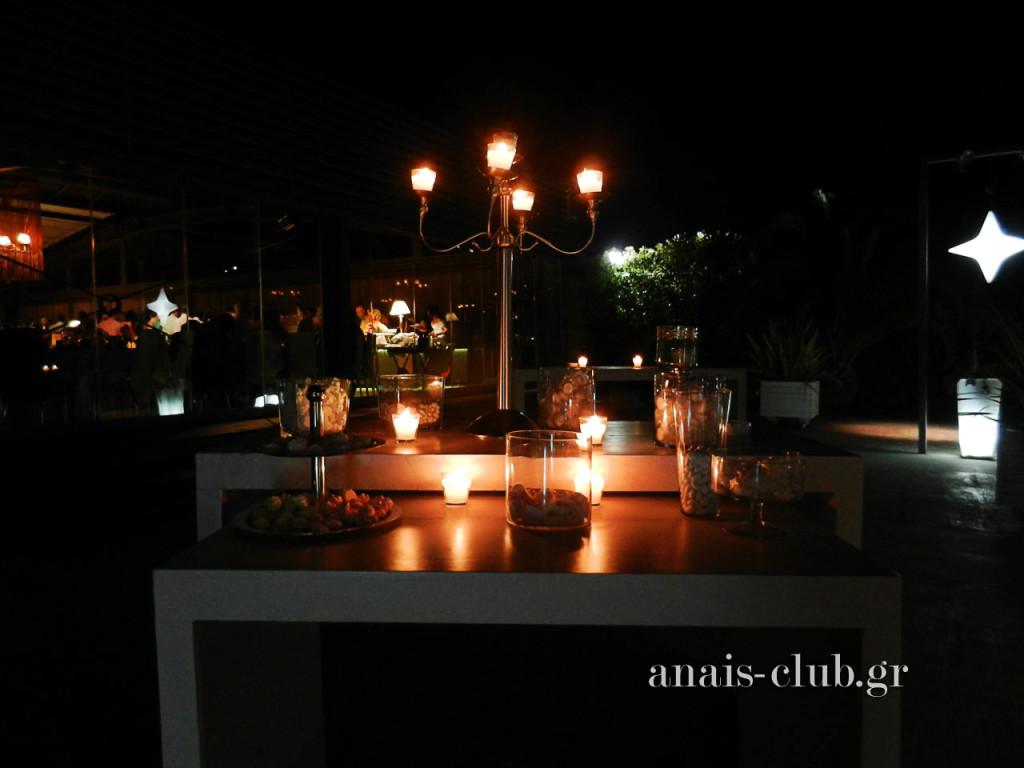 Το τραπέζι για το βιβλίο ευχών φωτίζεται από τη φλόγα των κεριών και είναι γεμάτο με κεράσματα και νόστιμα κουφέτα