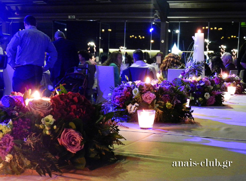 Συνθέσεις λουλουδιών σε λιλά χρώμα και κεριά, διακόσμησαν ανάλογα και το νυφικό τραπέζι. Σε αρμονία και ο στολισμός των λαμπάδων γάμου, που τοποθετήθηκαν στις άκρες μπροστά από το τραπέζι