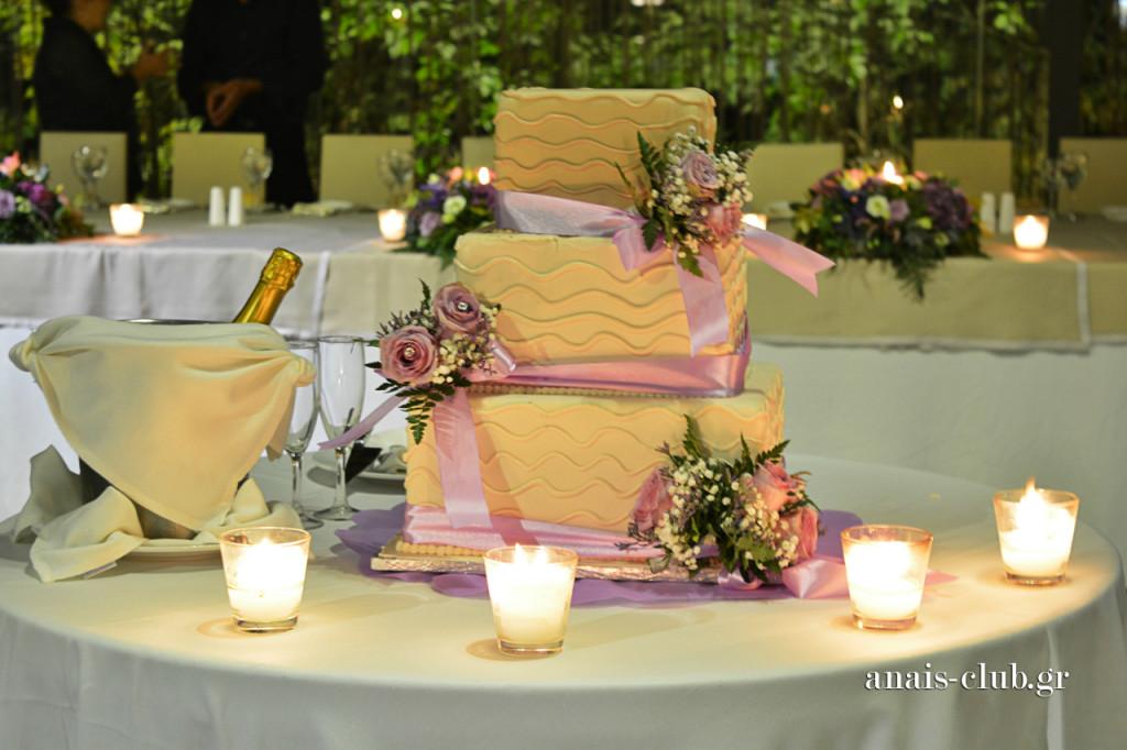 Η τετράγωνη τριώροφη τούρτα γάμου, είναι ένα από τα σχέδια που προτείνουμε στα ζευγάρια μας. Διακοσμείται κάθε φορά, ανάλογα με το ύφος και τα χρώματα του γάμου. Εδώ φυσικά έχει κυριαρχήσει το λιλά χρώμα.