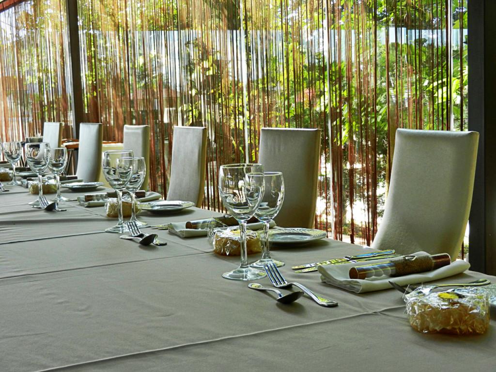 """Η κουρτίνα με τα κρόσσια πίσω από το νυφικό τραπέζι αφήνει το πράσινο του εξωτερικού χώρου να εισβάλει δυναμικά και να """"ταξιδέψει"""" τη φυσική ομορφιά και στο εσωτερικό"""