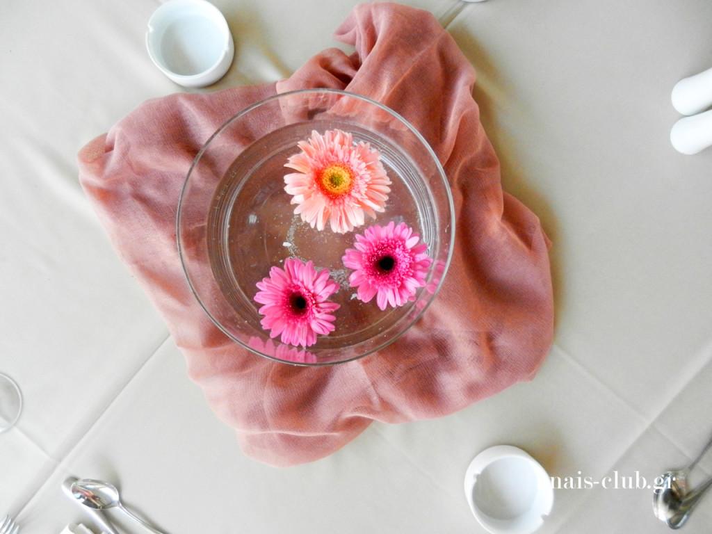 Οι γονείς της Λυδίας διάλεξαν να διακοσμήσουν το κέντρο των τραπεζιών με τις κυλινδρικές γυάλες που διαθέτουμε στα ζευγάρια που το επιθυμούν. Οι γυάλες γέμισαν με νερό και ροζ άνθη επέπλεαν σε αυτό. Ο στολισμός συμπληρώθηκε με ύφασμα σε ανάλογο χρώμα και τις μπομπονιέρες - πουγκιά στις θέσεις των καλεσμένων