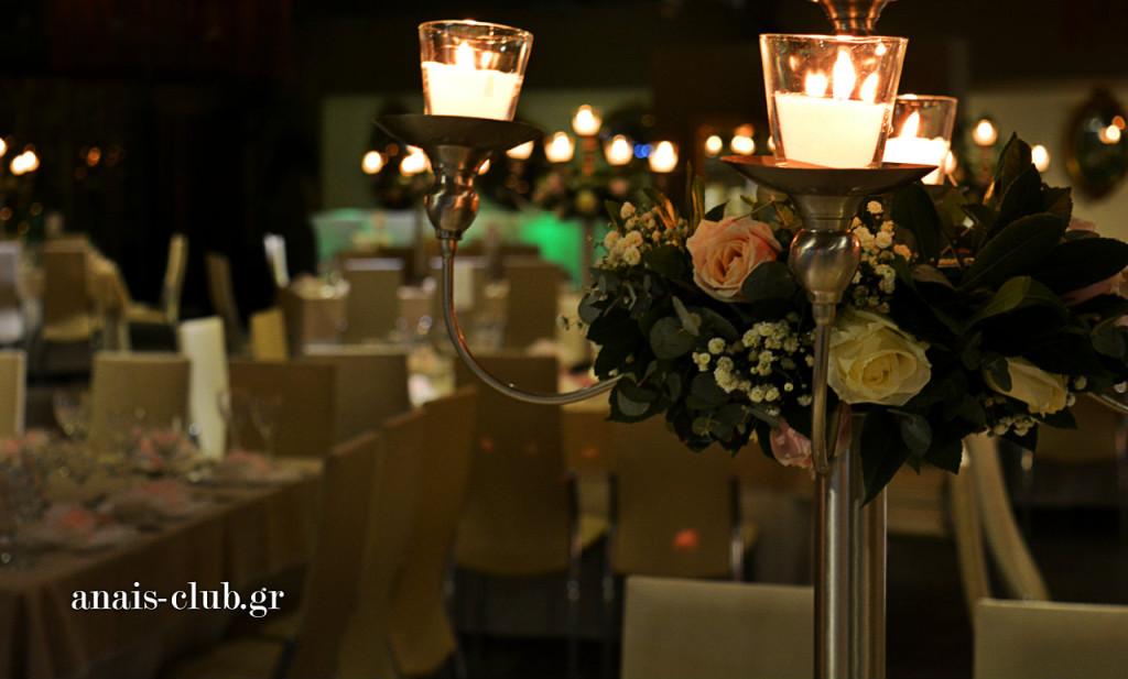 """Τα κεριά """"ζεσταίνουν"""" τον χώρο και ο στολισμός των κηροπήγιων με φρέσκα λουλούδια προσδίδει ρομαντικό χαρακτήρα στο σύνολο του κεντρικού στολισμού των τραπεζιών"""