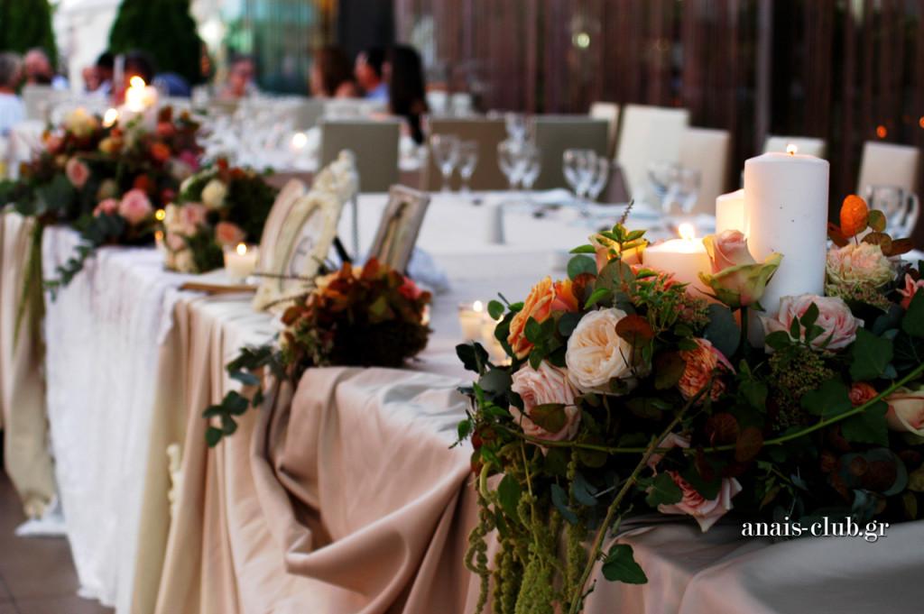 Λουλούδια και κεριά, σε εξαιρετικό συνδυασμό, στολίζουν το νυφικό τραπέζι