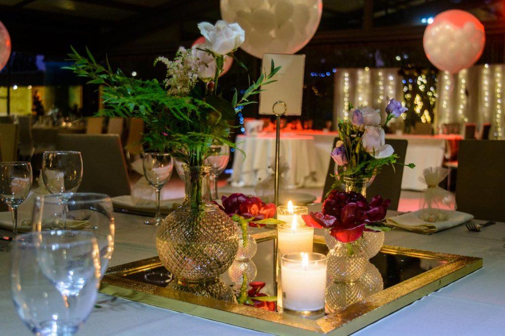 Centerpiece με κεριά και λουλούδια πάνω σε αντικέ καθρέφτη