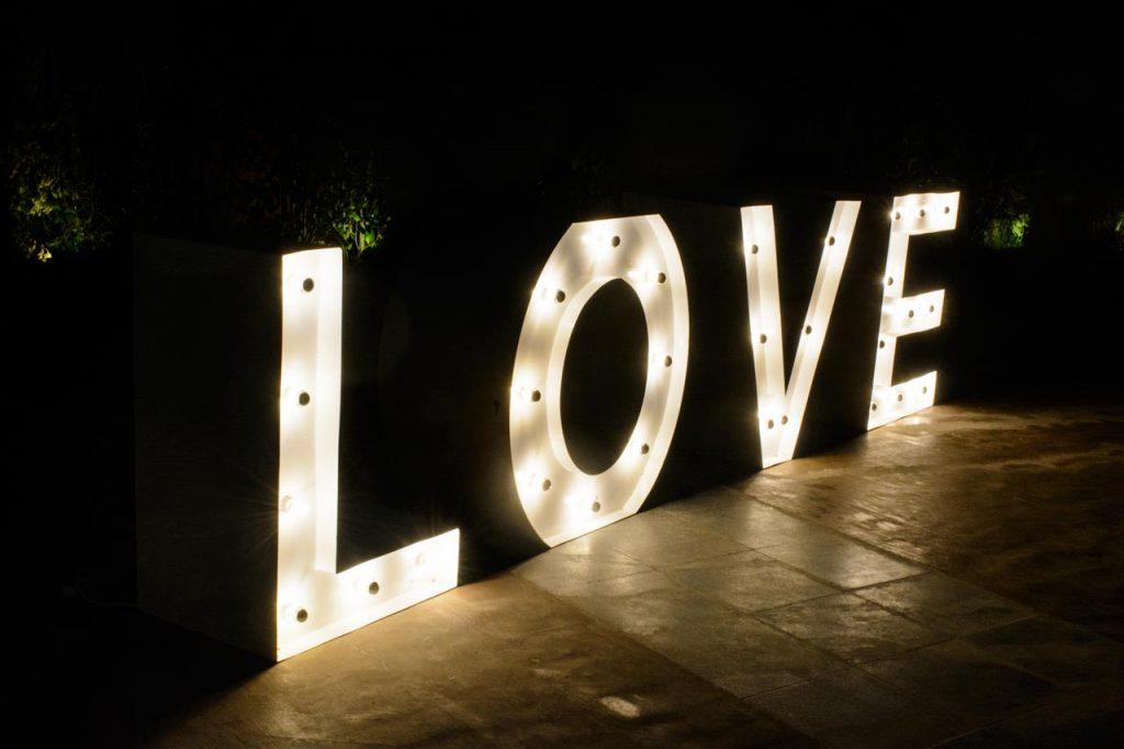 Φωτεινά γράμματα σχηματίζουν τη λέξη LOVE και είναι ένα τραπέζι για το βιβλίο ευχών ή το candy bar που προτείνουμε στα ζευγάρια
