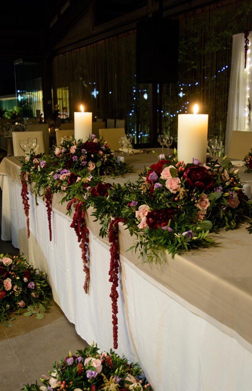 Στολισμός νυφικού τραπεζιού με λουλούδια και στοιχεία σε ζεστούς τόνους του κόκκινου, σε τόνους berry red